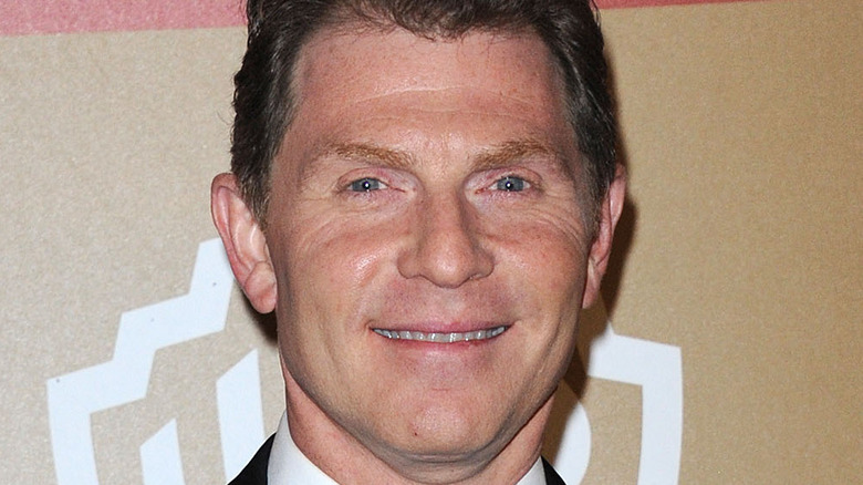 Bobby Flay smiles in a suit