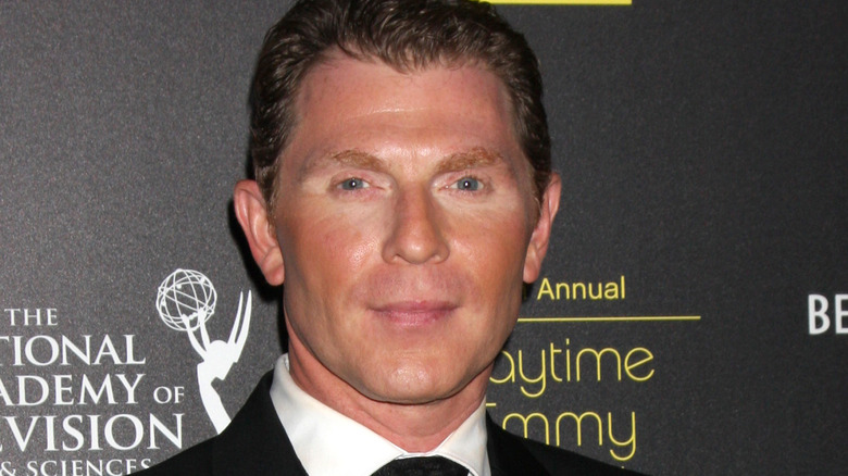 Bobby Flay smiles in suit and tie