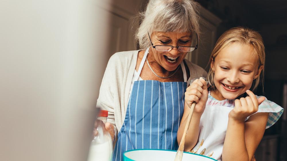grandma and girl baking a cake