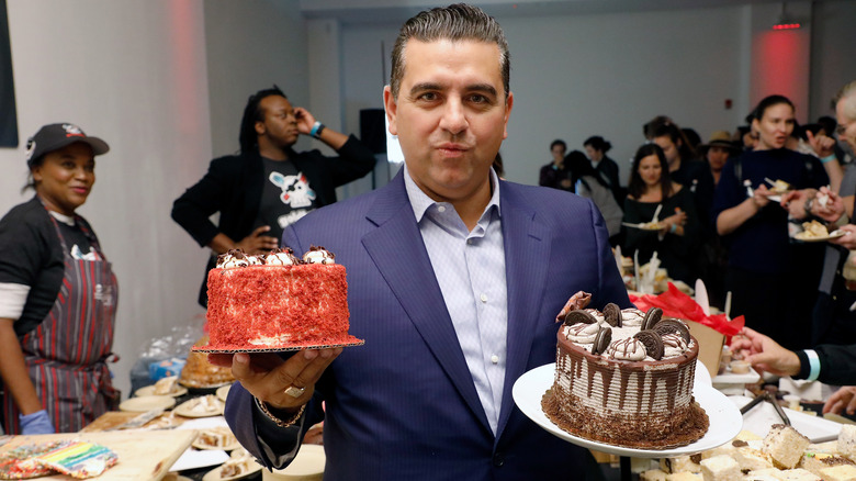 Buddy Valastro holding up two cakes