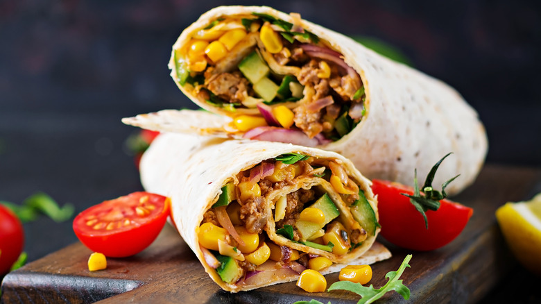 Burritos with beef and vegetables on a dark background