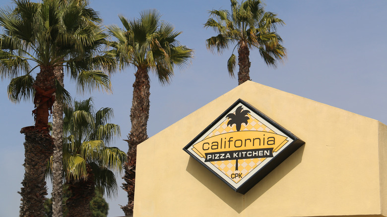 California pizza kitchen restaurant with palm trees in background