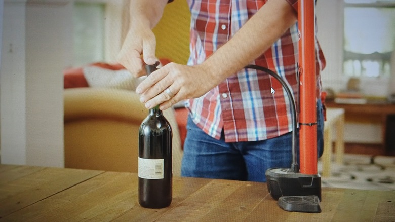 Man placing needle of bike pump into wine opening with cork