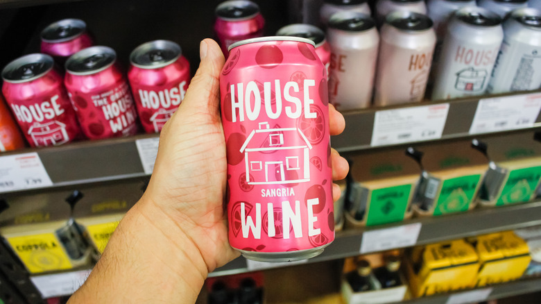 Hand holding a can of wine in aisle