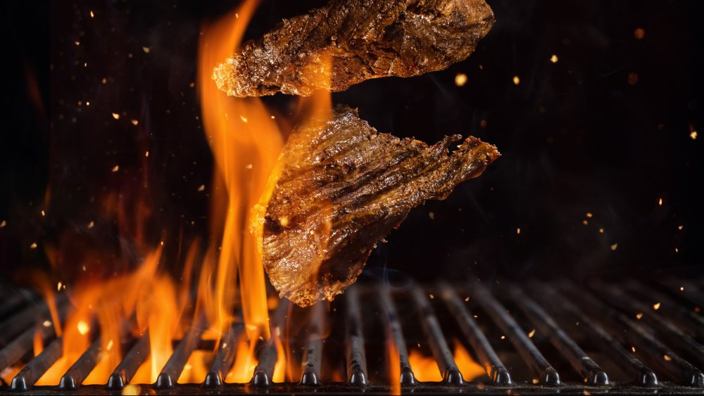 Beef steaks on flaming grill