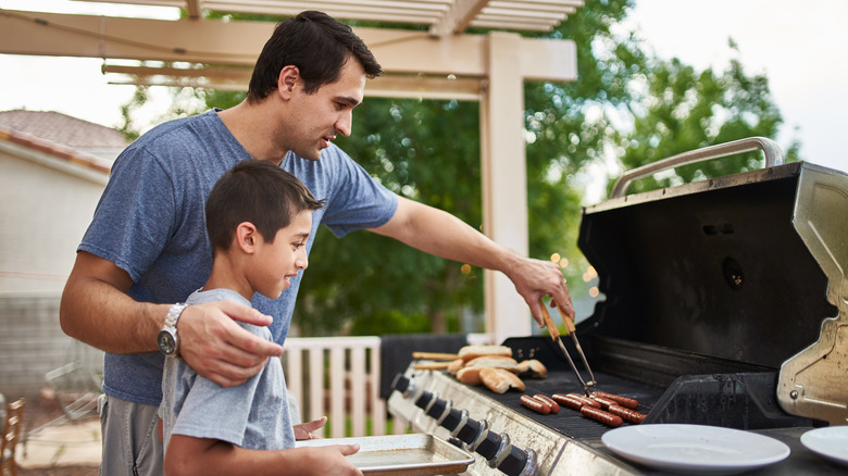 Person and child grilling hot dogs