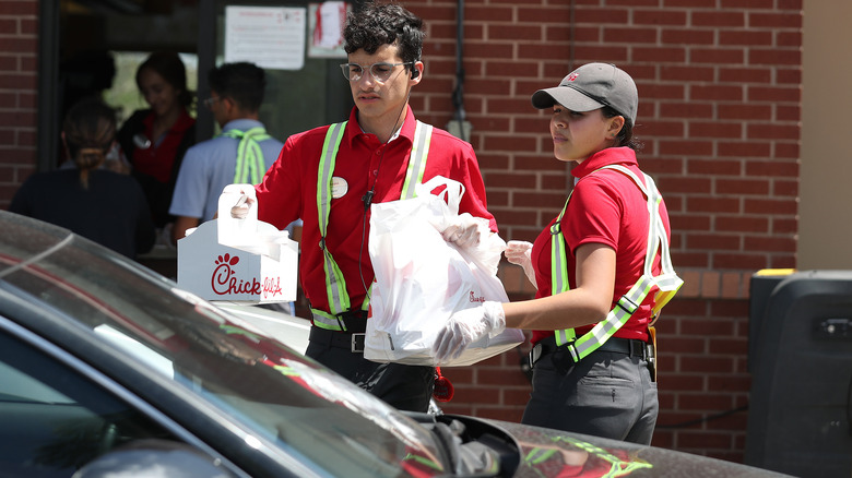 Chick-fil-A employee bringing order to car