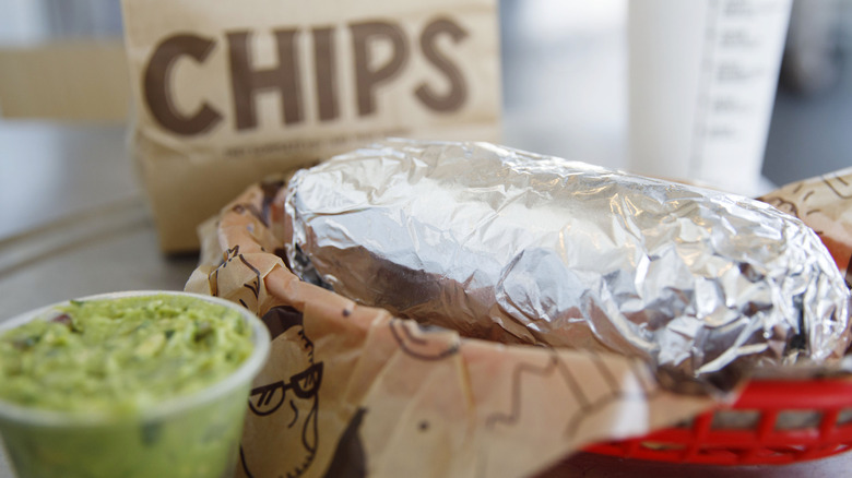 A Chipotle burrito with a side of chips and guacamole