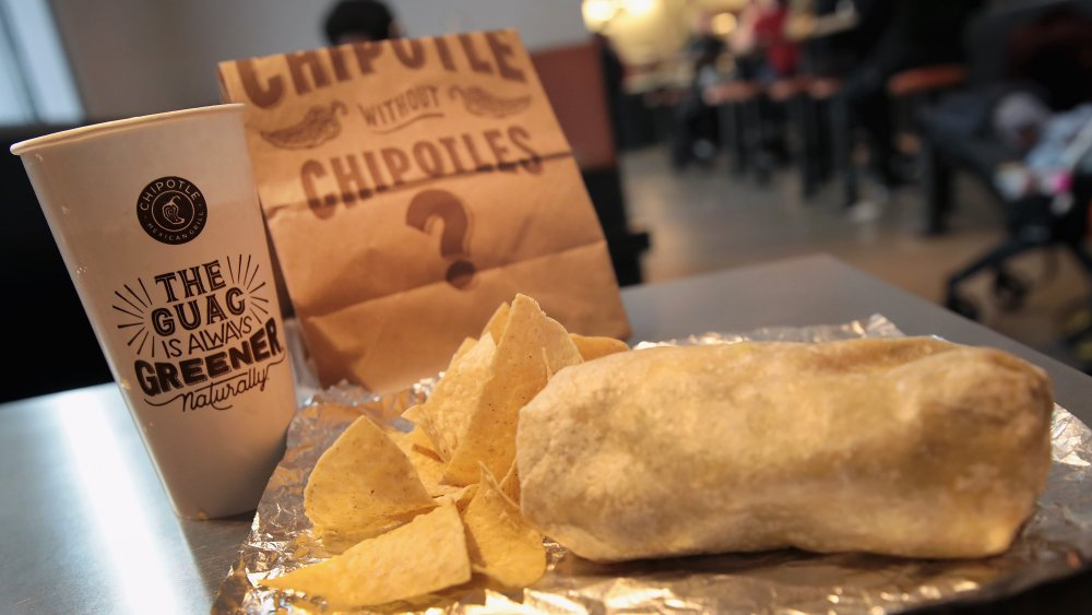 A Chipotle burrito with chips and a drink