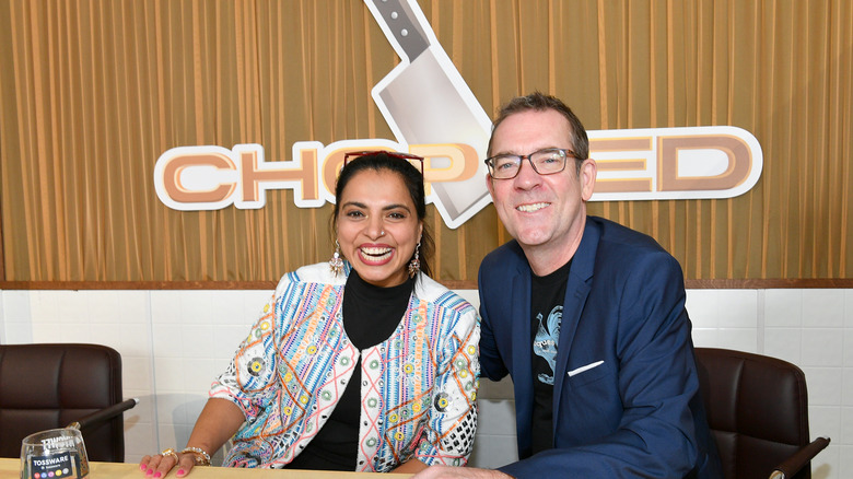 Maneet Chauhan and Ted Allen in front of Chopped logo