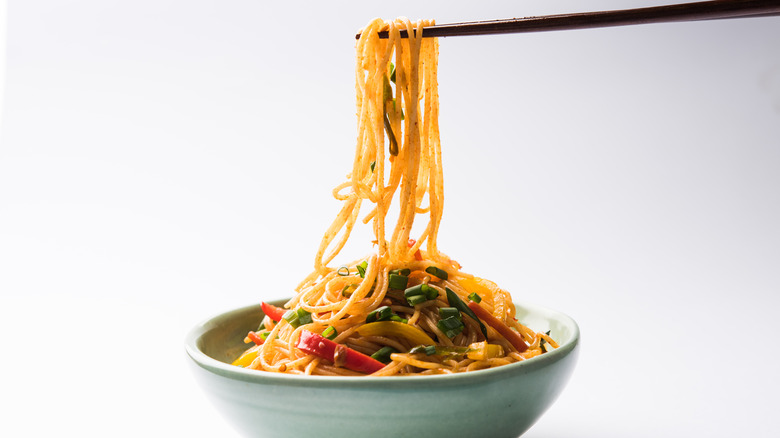 chopsticks holding chow mein noodles