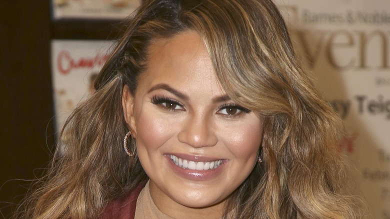 Chrissy Teigen smiling with hair down