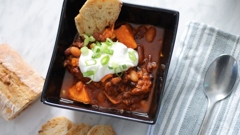 square bowl of chili with sour cream, baguette slices and green onions
