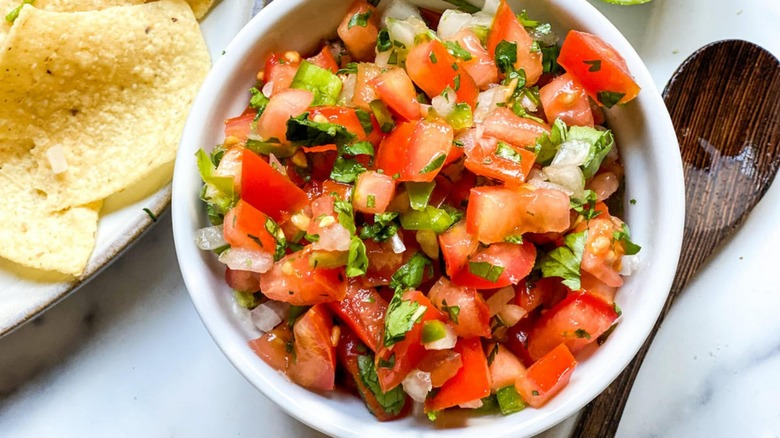 Overhead shot of a white bowl filled with pico de gallo next to a wooden spoon and a tomato