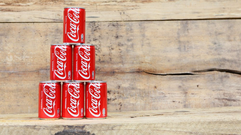 Cans of Coca-Cola stacked on wooden bench