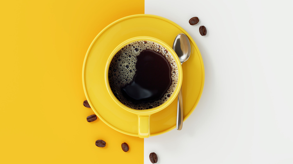 Coffee cup on yellow and white background