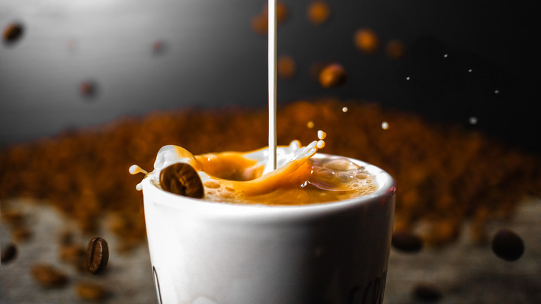 Cream falling into coffee in a white cup