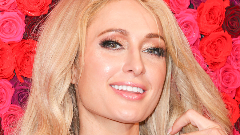 Paris Hilton smiling with a rose background