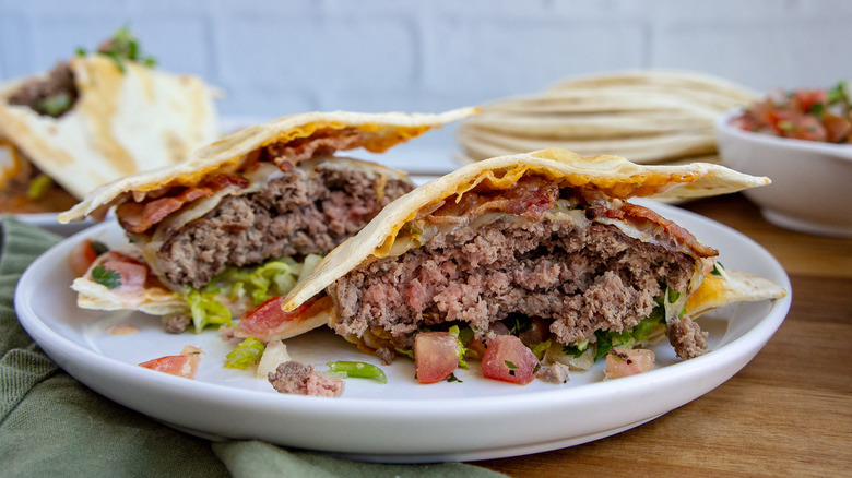 A burger between two small tortillas on a white plate