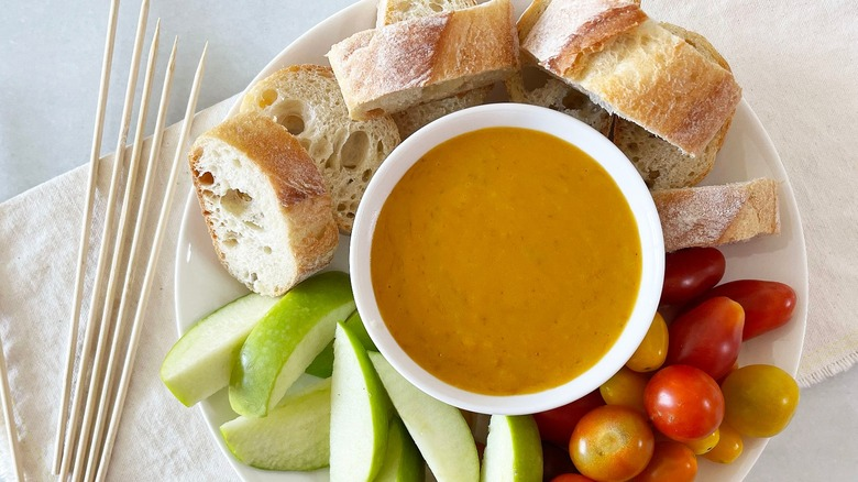 cheese fondue served with bread, apples, and tomatoes