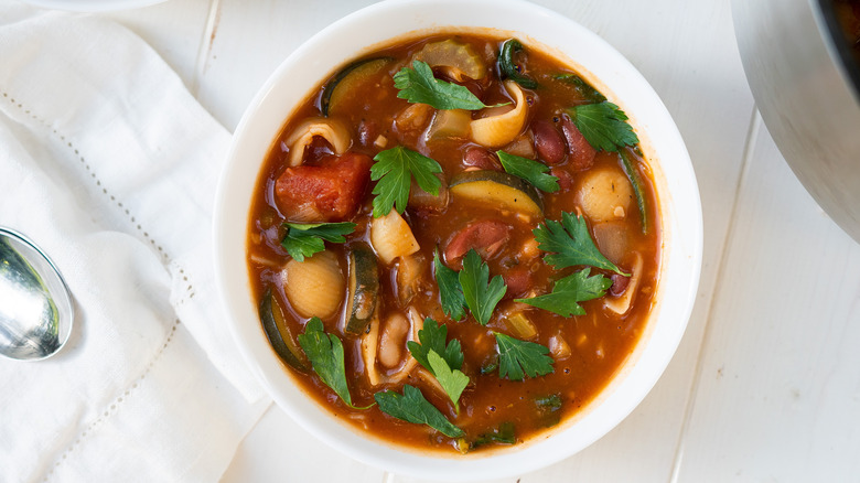 bowl of minestrone soup with parsley garnish