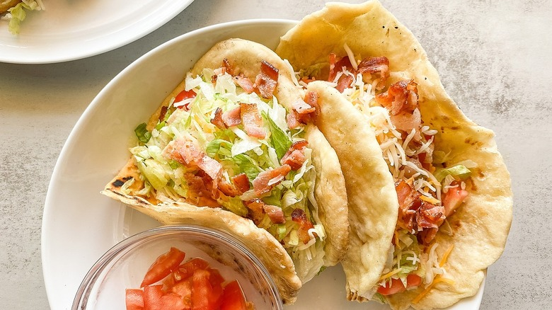 Bacon chalupas sitting on a plate with chopped tomatoes