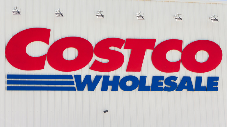 The Costco sign hanging on white building