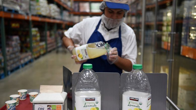 Costco employee pouring lemonade samples