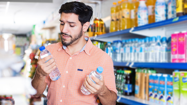 Person comparing bottles of water