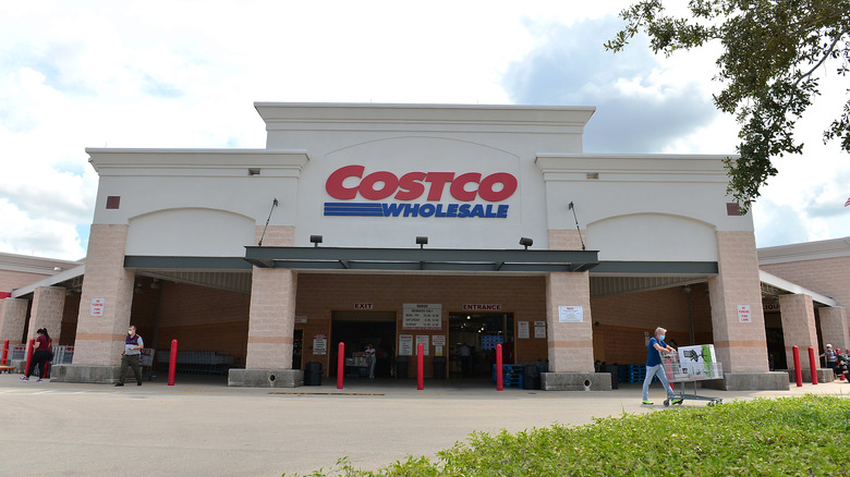 A giant Costco rears over a diminutive masked shopper as they cart away their boxed chair, the gift of the changeable savings brand.