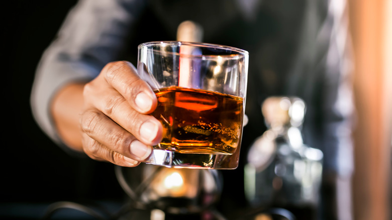 Bartender holding out glass of scotch