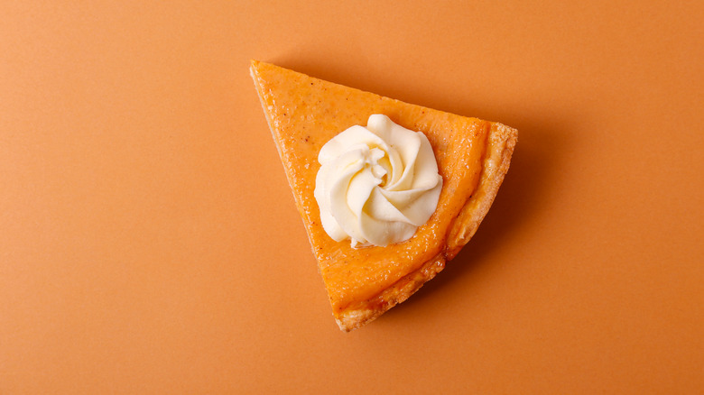 Slice of pumpkin pie with whipped cream on top