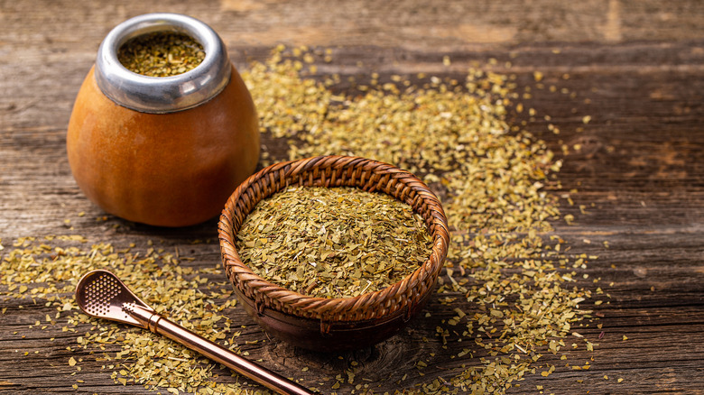 Small basket and traditional container of dry yerba mate tea with spoon