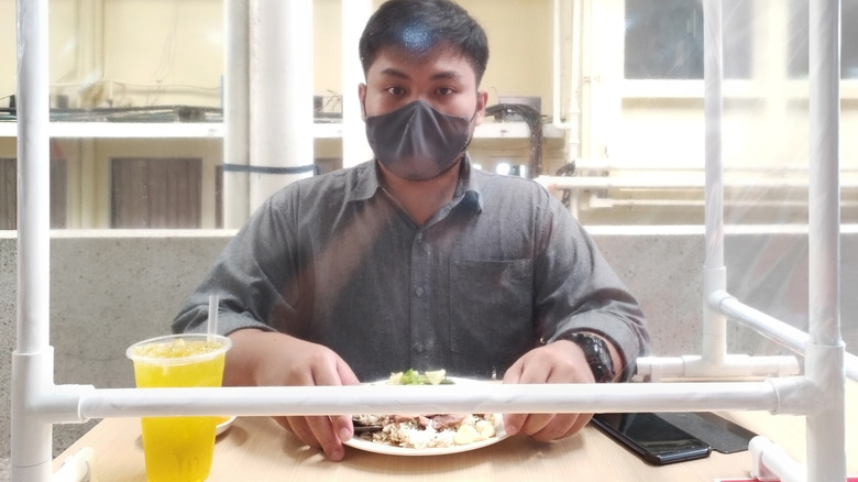 Person eating meal behind barrier