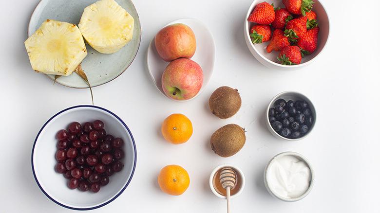 Cut pineapples next to red grapes, apples, tangerines, kiwis, honey, yogurt, blueberries, and strawberries