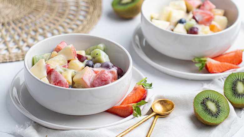 Two white bowls of fruit salad on two small white plates next to strawberries, kiwis, and gold spoons
