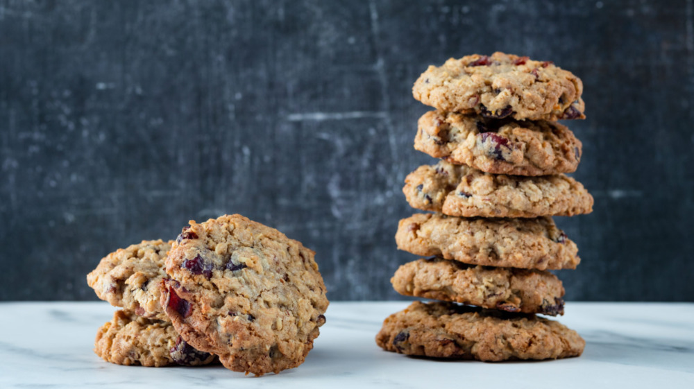 cranberry orange oatmeal cookies stacked on a white counter