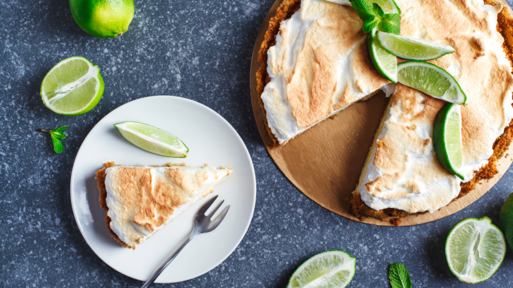 key lime pie slice on a plate with fresh limes
