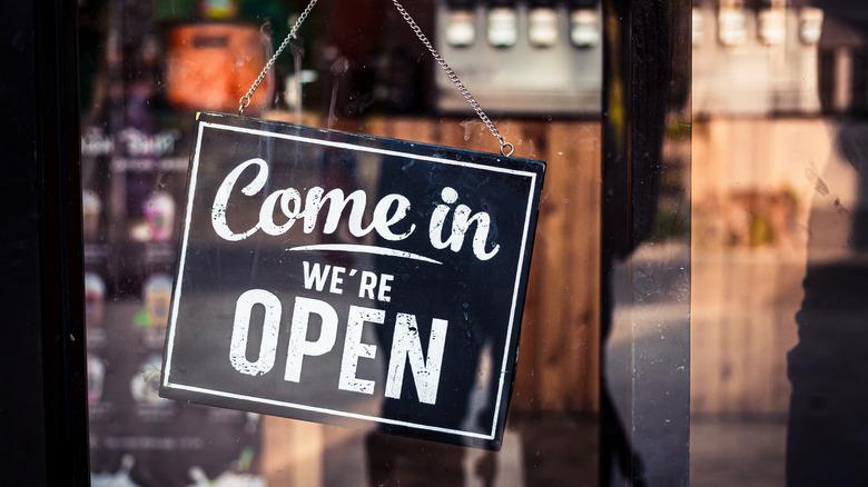 """""""Come In, We're Open"""" sign on restaurant door"""