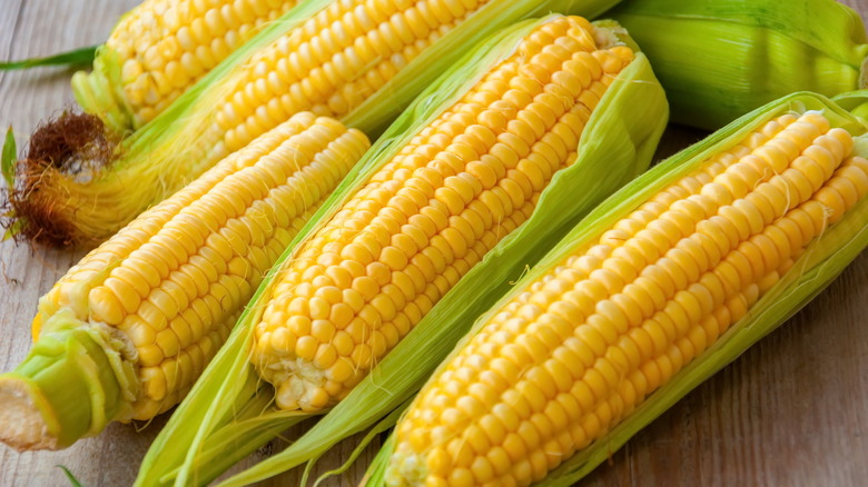 four fresh corn cobs on a wooden table