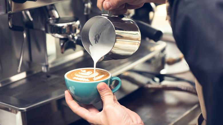 Barista pouring milk into an espresso mug