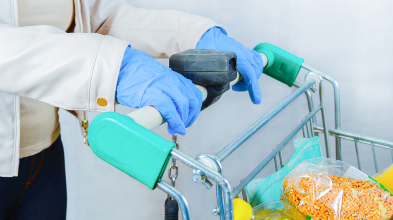 Grocery shopper wearing latex gloves