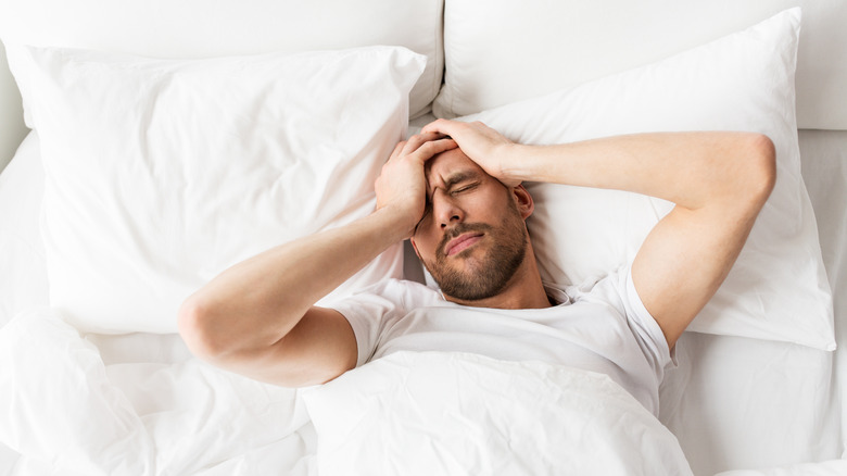 A man in a bed with a hangover headache