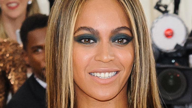 Beyoncé wears a beige dress with straight hair