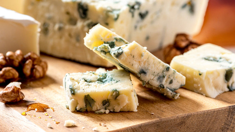 Sliced blue cheese on cutting board