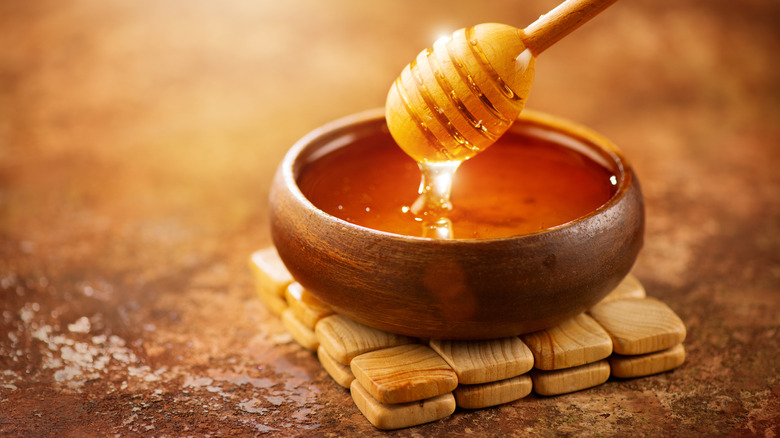 bowl of honey with wooden dipper