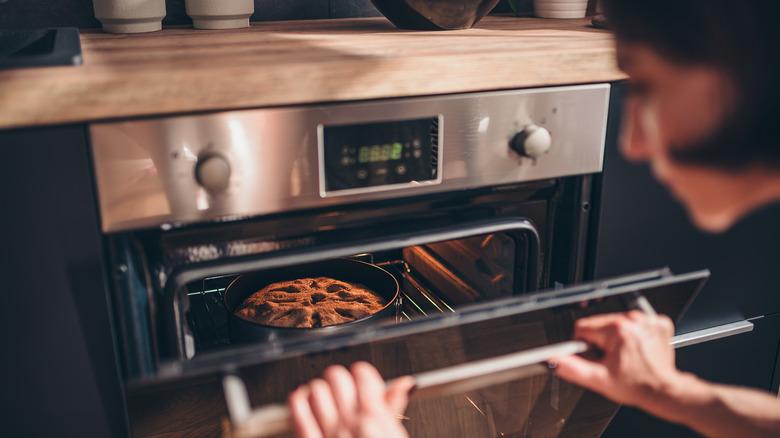 Hands opening oven door with cake baking inside