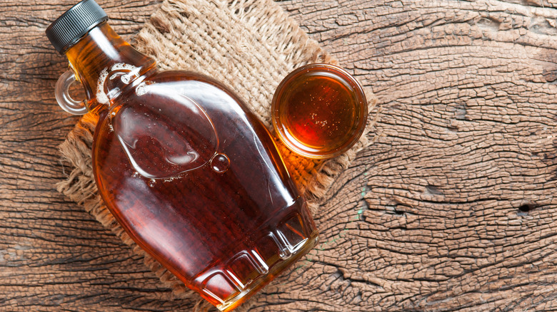 Bottle of maple syrup on a wooden board