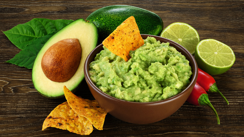 Bowl of guacamole and chips next to avocado