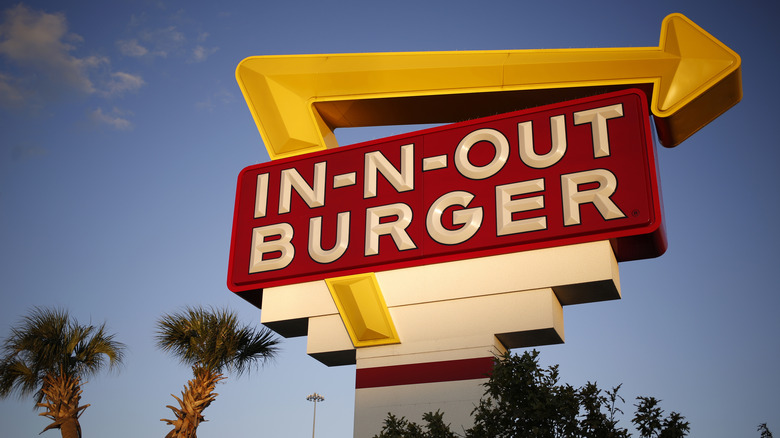 An In-N-Out road sign with palm trees and blue sky in the background